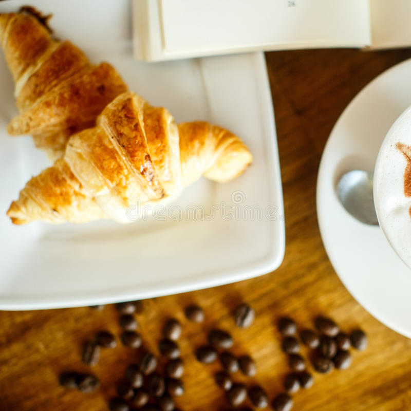 Cappuccino e croissant com feijão e livros de café imagens de stock royalty free