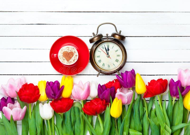 Cappuccino e pulso de disparo perto das flores imagens de stock royalty free