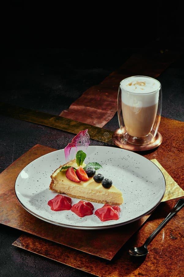 Cappuccino e torta di formaggio con le fragole, i mirtilli e la menta su un piatto bianco su un fondo di rame fotografia stock