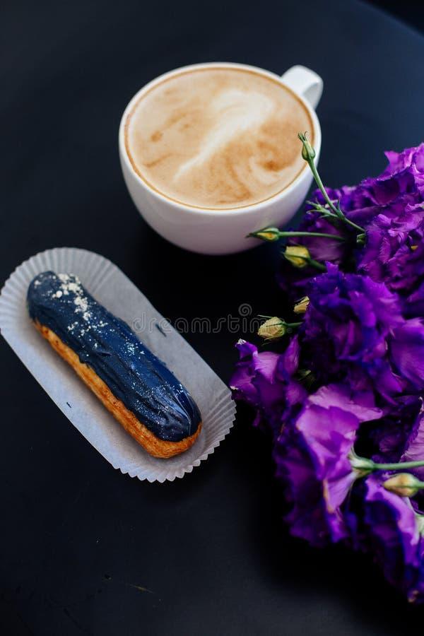 Cappuccino, eclairs e flores imagens de stock