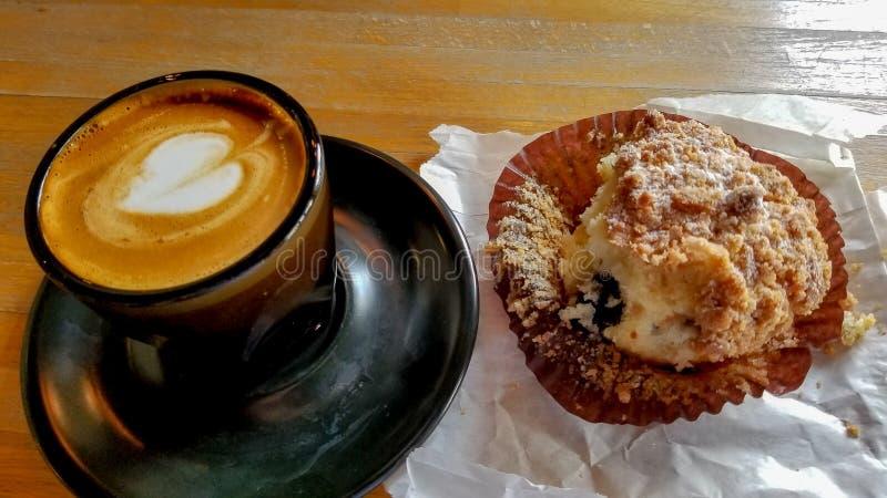 Cappuccino in einer schwarzen keramischen Tasse und Untertasse, nahe bei Blaubeerkaffeekuchenmuffin lizenzfreies stockfoto