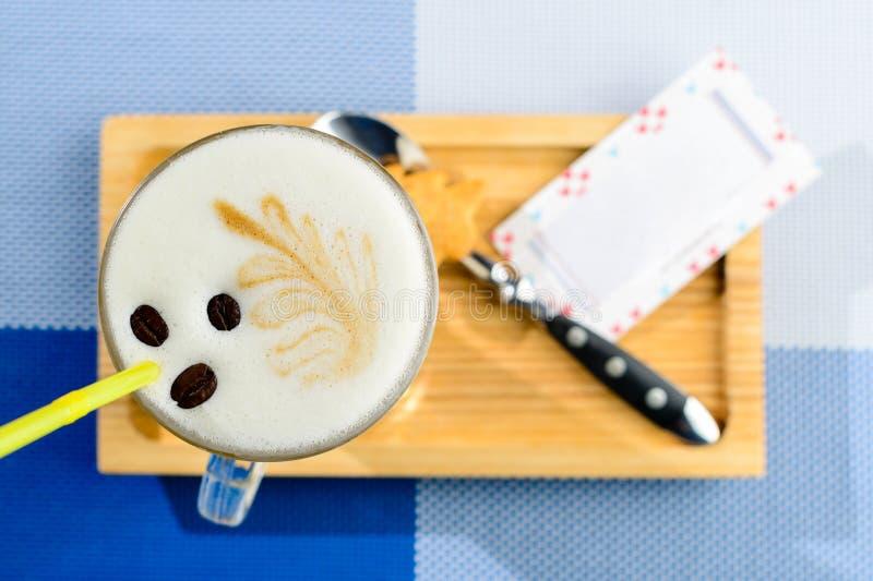 Cappuccino em um vidro na placa de madeira e cartão com copyspac imagens de stock royalty free