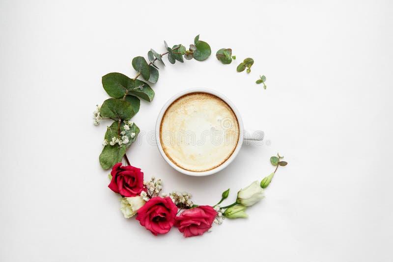 Cappuccino en bloemensamenstelling Witte koffiekop met romig schuim, verse bloemencirkel bij witte, hoogste mening heet royalty-vrije stock afbeelding