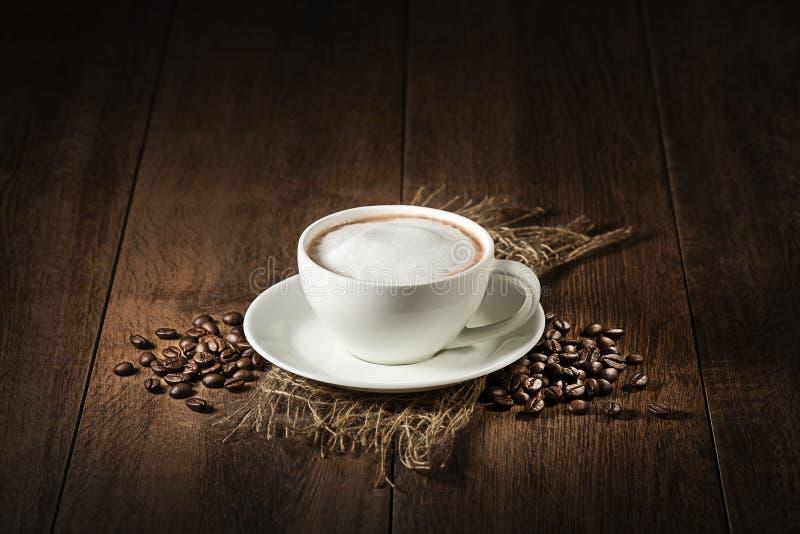 Cappuccino filiżanka z kawowymi fasolami zdjęcia stock