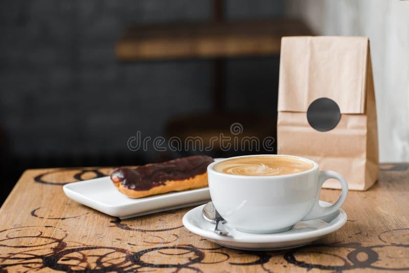 Cappuccino flatwhite Kaffee mit Eclair lizenzfreies stockbild