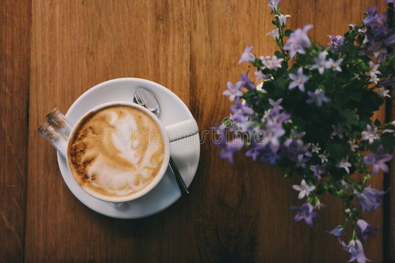 Cappuccino and flowers stock photography