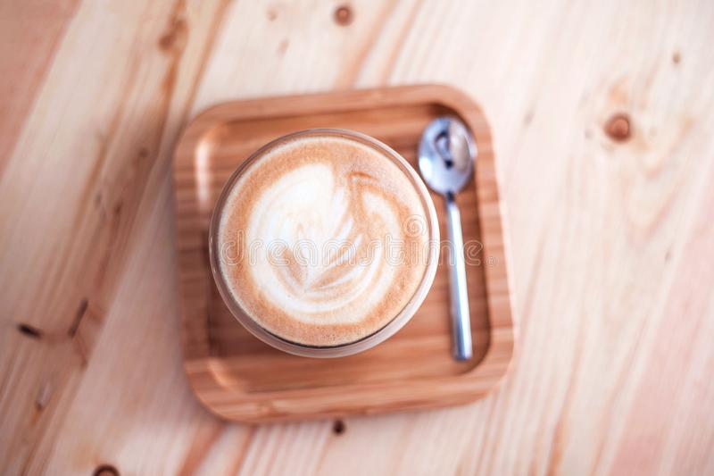 Fresh flavored coffee art on wooden background. Cappuccino with frothy foam, glass coffee cup top view closeup on white wood background. Flat lay style royalty free stock image