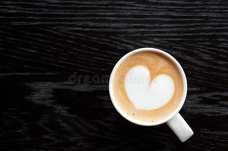 Cappuccino with heart shape foam in a white ceraamic mug isolated on dark brown wood table with grain from above. Space for text.  royalty free stock photo