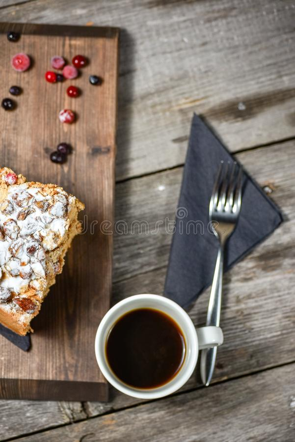 Coffee and homemade cake with nuts and fruits on dark wood background, recipe. Top flat view, from above. stock image