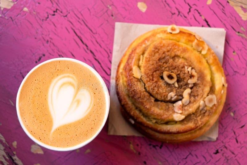 Cappuccino i cynamonu ciasta rolka odizolowywająca na malował drewno z góry obrazy stock