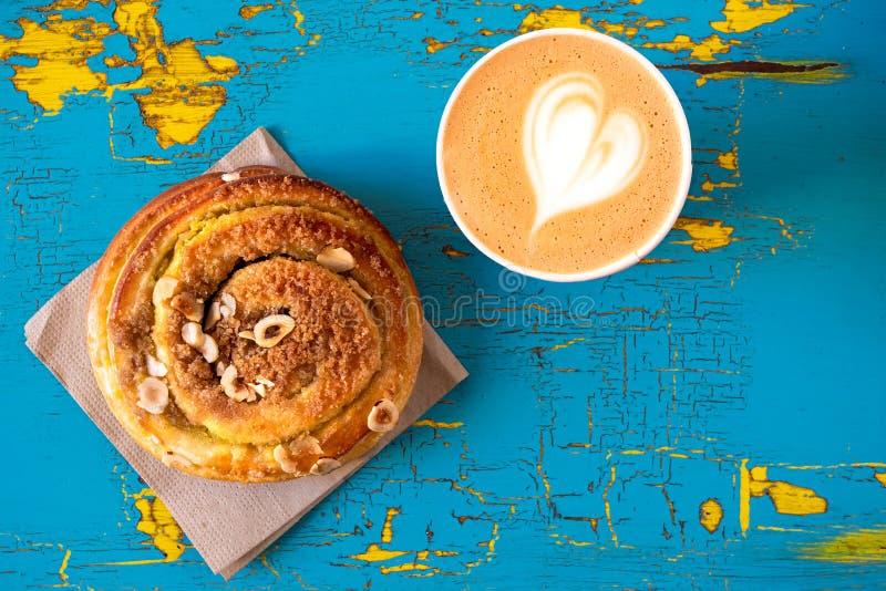 Cappuccino i cynamonu ciasta rolka odizolowywająca na malował drewno z góry Przestrze? dla teksta zdjęcia royalty free