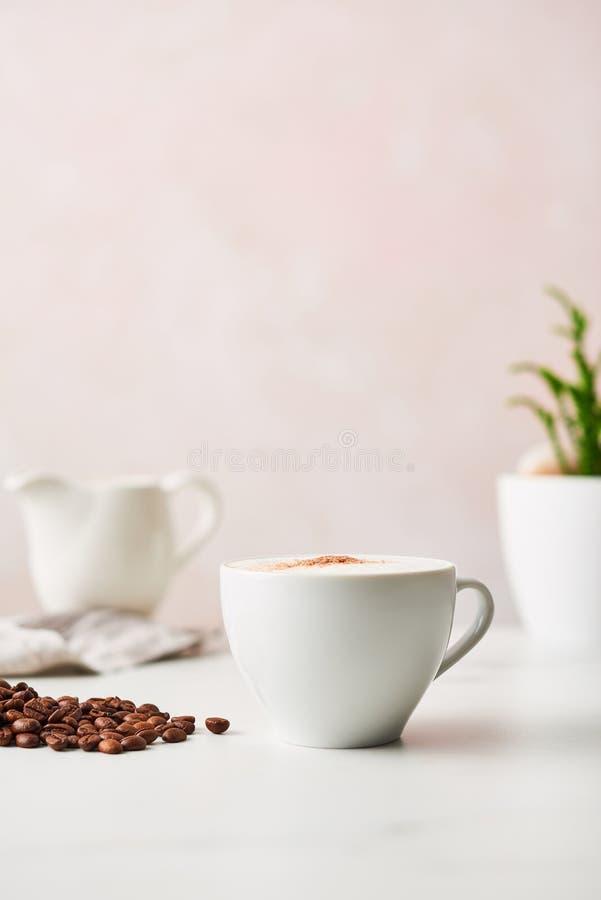 Cappuccino i en vit keramisk kaffekopp med grillad kaffebea royaltyfria bilder