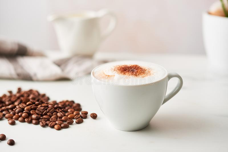 Cappuccino i en vit keramisk kaffekopp med grillad kaffebea arkivbild