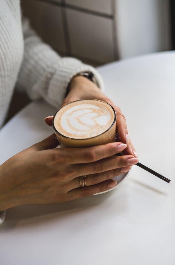 Cappuccino i ett exponeringsglas på den vita tabellen av kafét royaltyfria foton