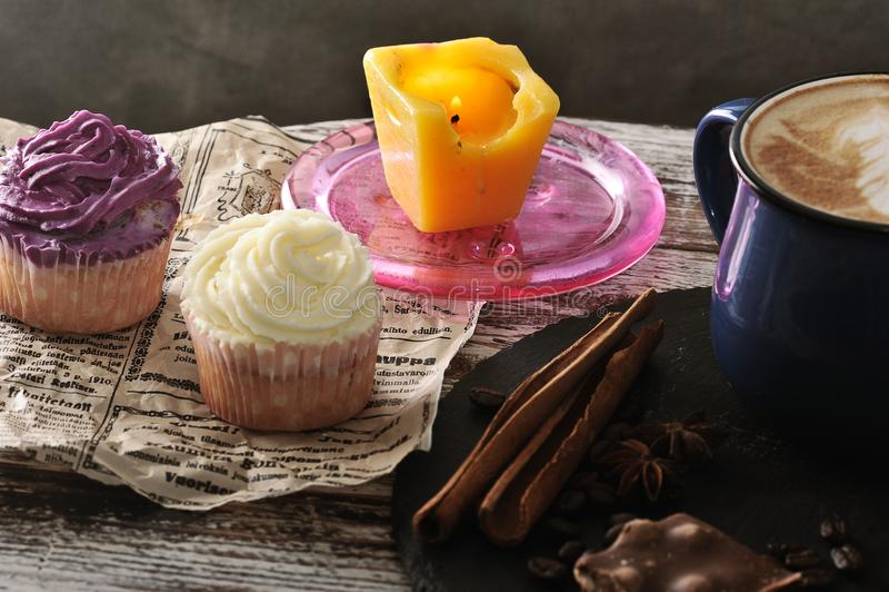 Cappuccino im Becher mit Milchschaum und zwei kleine Kuchen und eine Kerze lizenzfreie stockfotos