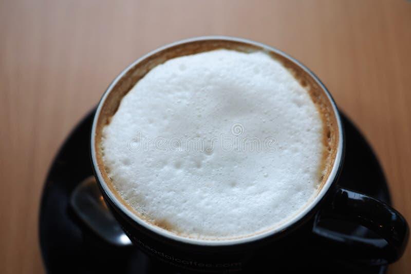Cappuccino kawa z bielu mleka piany czerni filiżanki drewnianym stołem zdjęcia stock