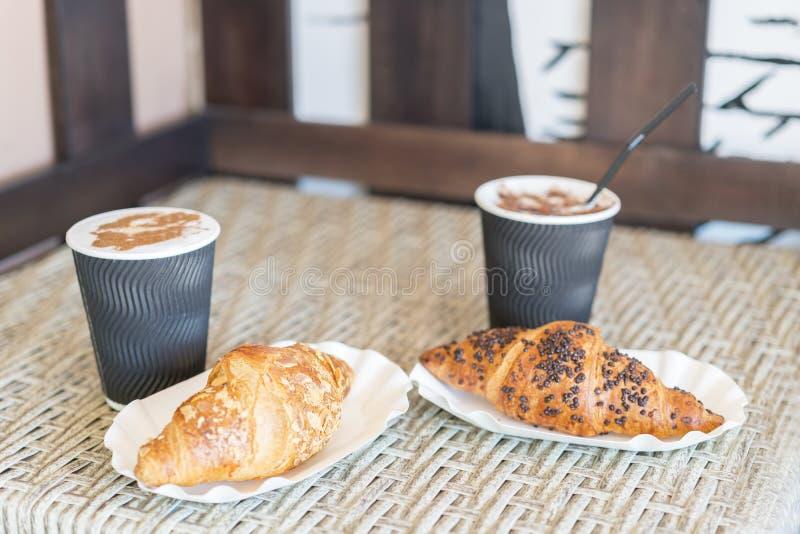 Cappuccino met croissant Twee koppen van koffie met de tribunes van het melkschuim op een lijst in cafetaria Twee koppen van koff royalty-vrije stock fotografie