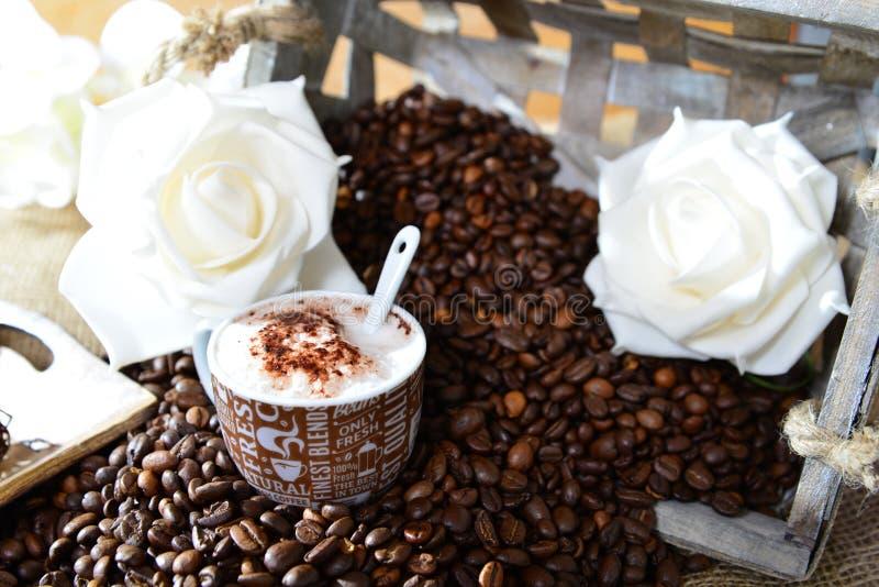 Cappuccino met koffiebonen en rozen stock foto