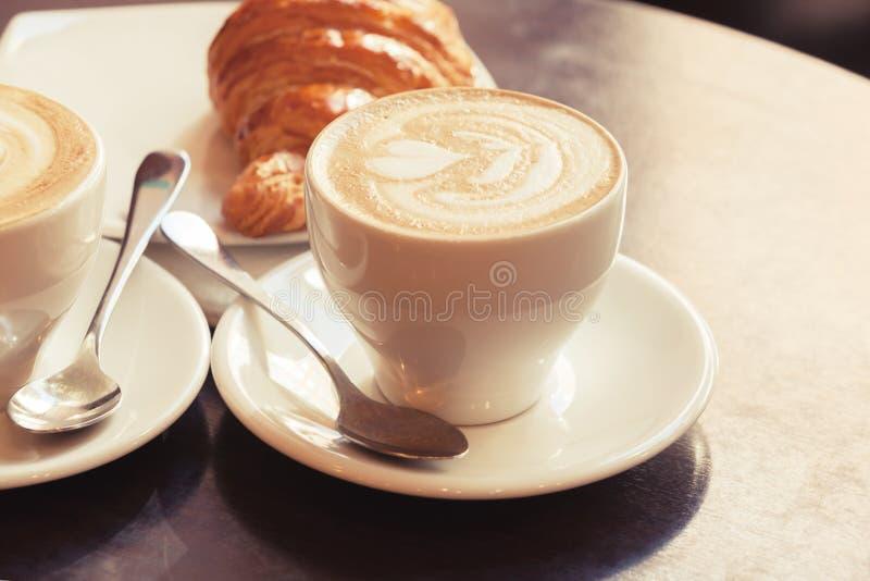 Cappuccino mit Hörnchen Zwei Tasse Kaffees auf Tabelle lizenzfreies stockbild