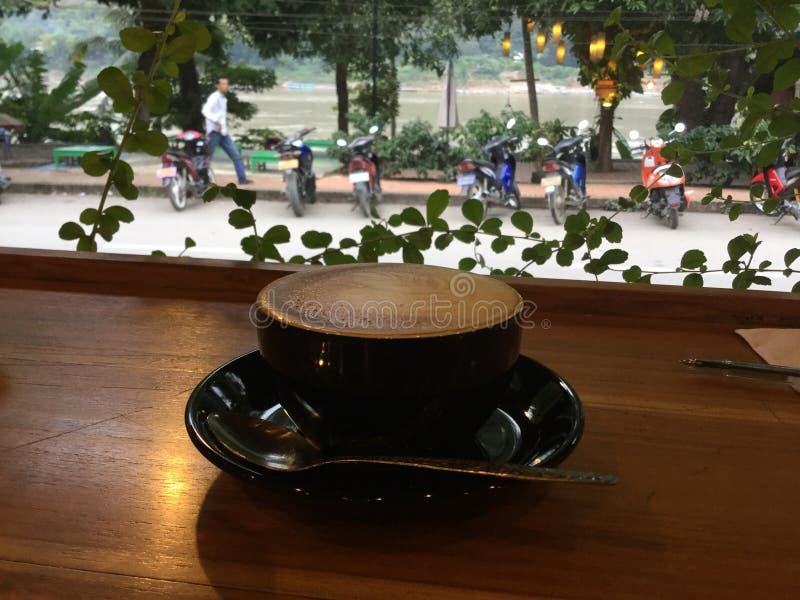 Cappuccino na barra de madeira Fundo de Mekong River imagem de stock