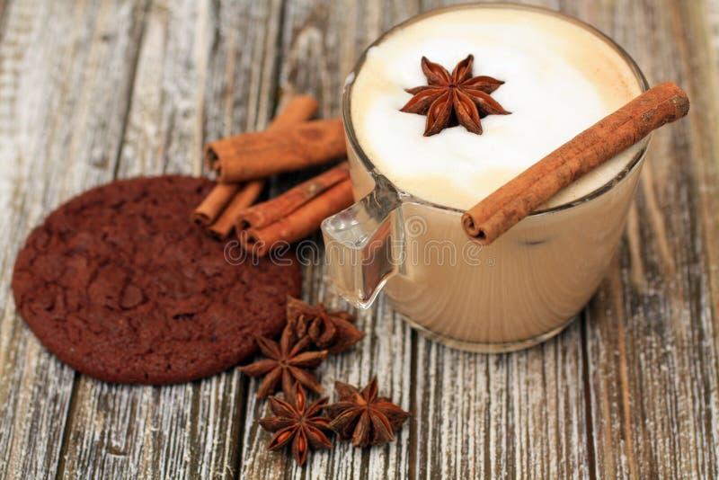 Cappuccino och kaka med stjärnaansie och den kanelbruna pinnen arkivfoton