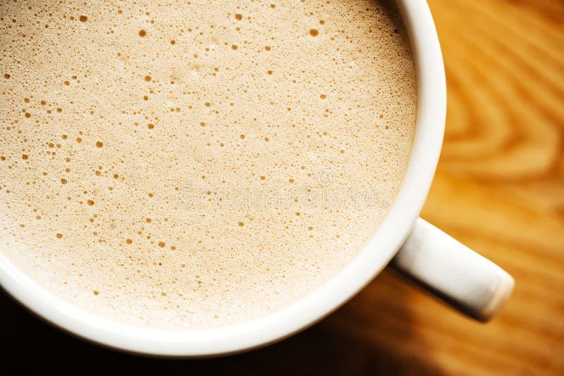 Cappuccino oder Latte mit schaumigem Schaum, Draufsichtnahaufnahme der Kaffeetasse auf hölzernem Hintergrund Café und Stange stockfoto