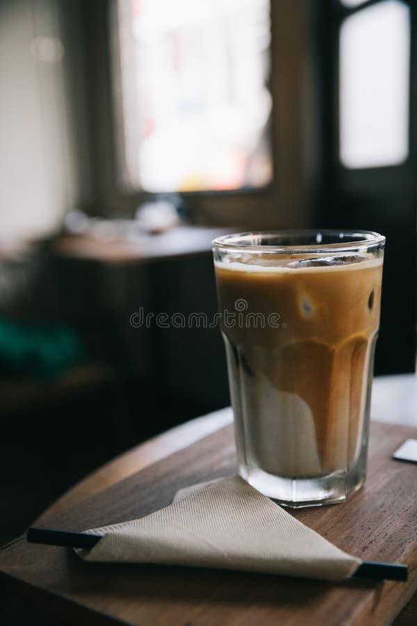 Cappuccino oder Latteeiskaffee machten von der Milch auf dem Holztisch in der Kaffeestube lizenzfreies stockbild
