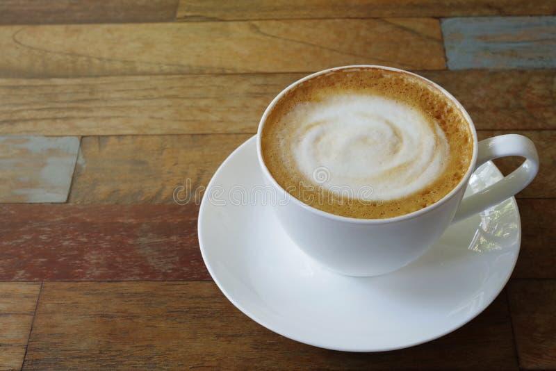 Cappuccino ou latte de tasse de café chaud avec mousse de lait en spirale agitée sur fond de table en bois en planche multicolor image stock