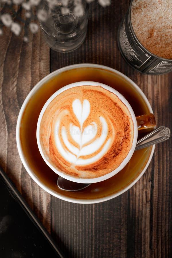 Cappuccino på den bruna trätabellen i en kopp och ett tefat bredvid socker, blommor och en mobiltelefon royaltyfri fotografi
