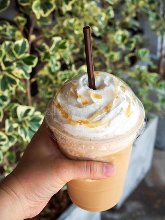 Cappuccino in plastic kop wordt gemengd die Gediend met slagroom Verfrissingdrank Favoriete cafe?nedrank royalty-vrije stock afbeeldingen