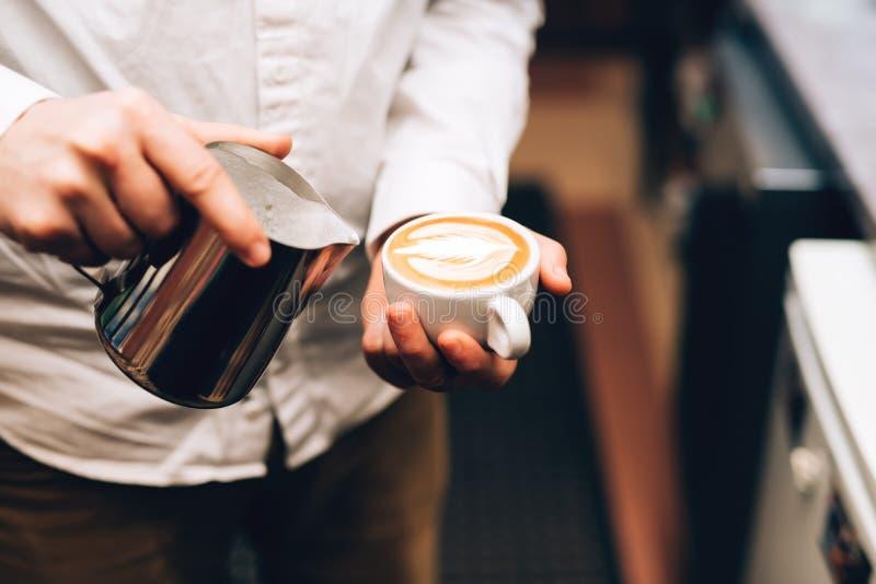 Cappuccino se renversant de barman dans la tasse, faisant une boisson délicieuse de matin images libres de droits