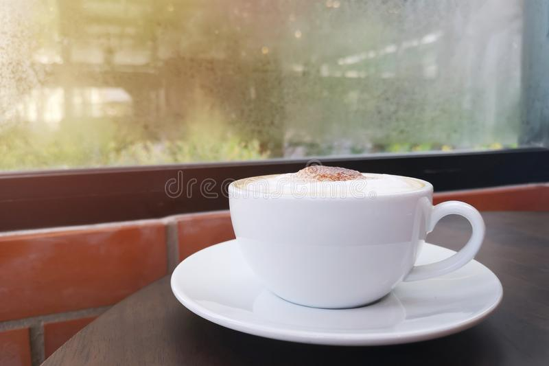 Cappuccino served hot. drink made from white coffee cup on the wooden table  beside the window. stock image