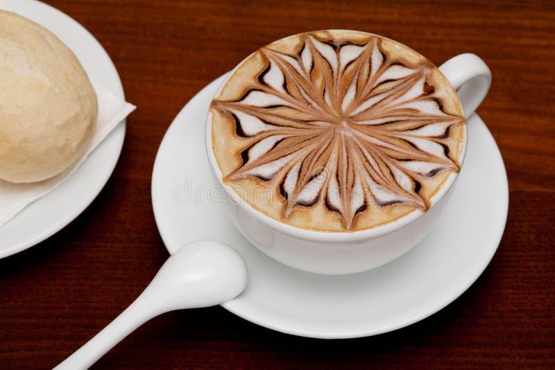 Cappuccino, taza de café y bollo fotografía de archivo libre de regalías