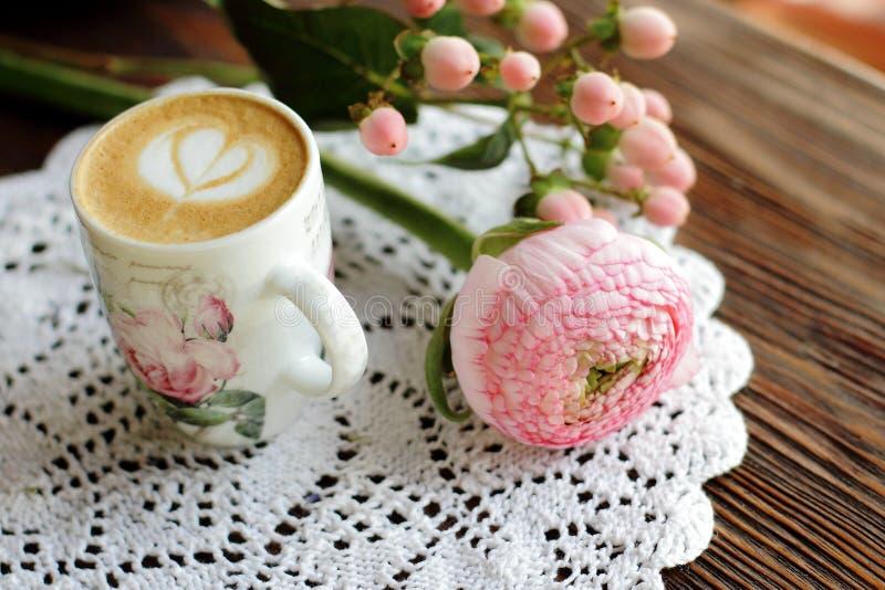 Cappuccino in uitstekende kop met bloemontwerp en gebreid servet royalty-vrije stock afbeelding
