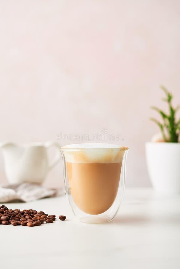 Cappuccino in un vetro a doppia parete con i chicchi di caffè arrostiti immagini stock libere da diritti