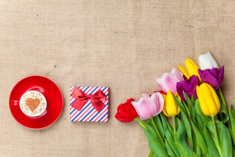 Cappuccino und Geschenkbox nahe Blumen lizenzfreie stockbilder