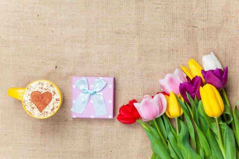 Cappuccino und Geschenkbox nahe Blumen stockfoto
