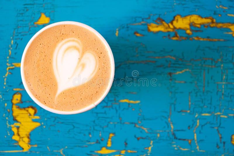 Cappuccino w papierowym bierze oddaloną filiżankę na i kolor żółty malującego drewno z góry obieraniu i pękającym błękicie Przest fotografia royalty free