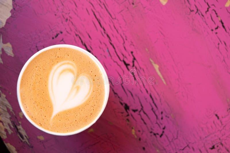 Cappuccino w papierowym bierze oddaloną filiżankę odizolowywającą na obieraniu i pękającym menchia malującym drewnie z góry Przes obraz stock