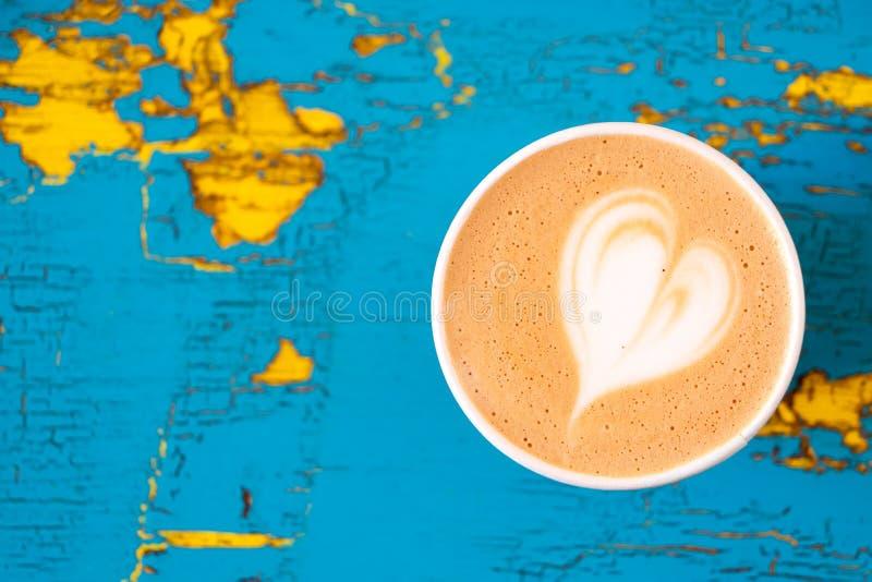 Cappuccino w papierowym bierze oddaloną filiżankę odizolowywającą na z góry i kolor żółty malującego drewno obieraniu i pękającym obraz royalty free