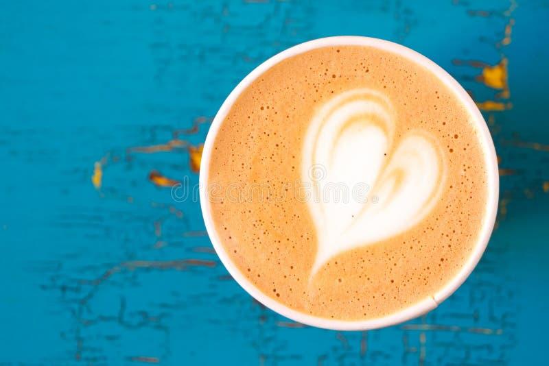 Cappuccino w papierowym bierze oddaloną filiżankę odizolowywającą na z góry i kolor żółty malującego drewno obieraniu i pękającym zdjęcia stock
