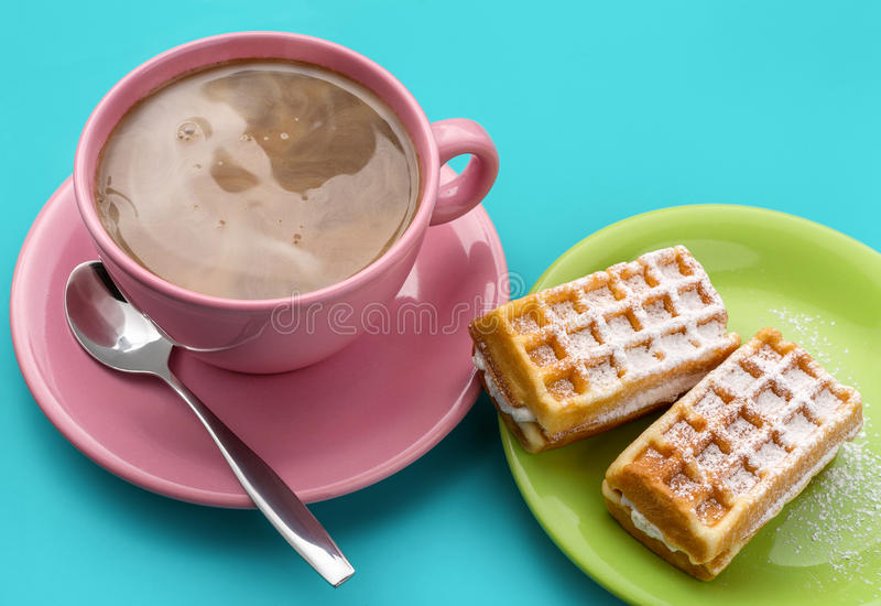 Cappuccino and waffles. Hungarian waffles and a large cup of cappuccino coffee on a blue background royalty free stock image