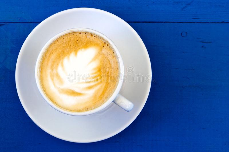Cappuccino in white ceramic cup with saucer on blue painted wood. From above stock photos