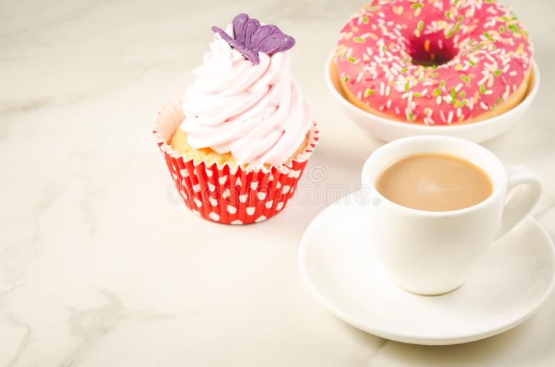 Cappuccino white cup and fresh cake with butterfly/cappuccino white cup and fresh cake with butterfly on a white marble. Background. Selective focus and royalty free stock images
