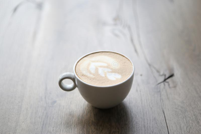 Cappuccino in white glass with wire drawing on milk froth royalty free stock photos