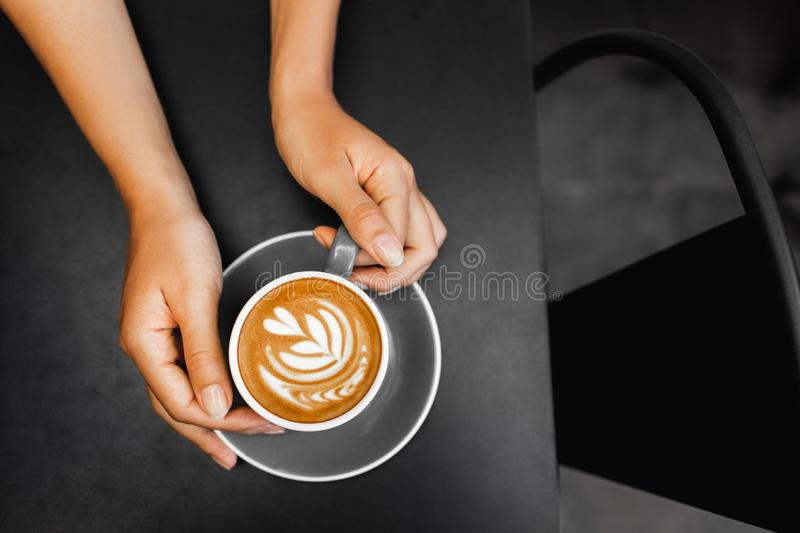 Cappuccino in woman hands on dark black background. Cup of fresh cappuccino in woman hands on dark black metal table background. Empty place for text. Coffee stock photos