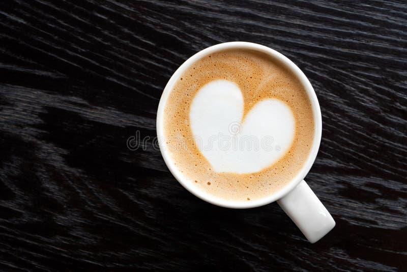 Cappuccino z kierową kształt pianą w białym ceraamic kubku odizolowywającym na ciemnego brązu drewna stole z adrą z góry Przestrz obraz stock