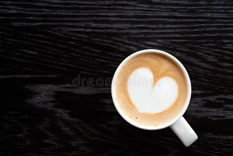 Cappuccino z kierową kształt pianą w białym ceraamic kubku odizolowywającym na ciemnego brązu drewna stole z adrą z góry Przestrz zdjęcie royalty free