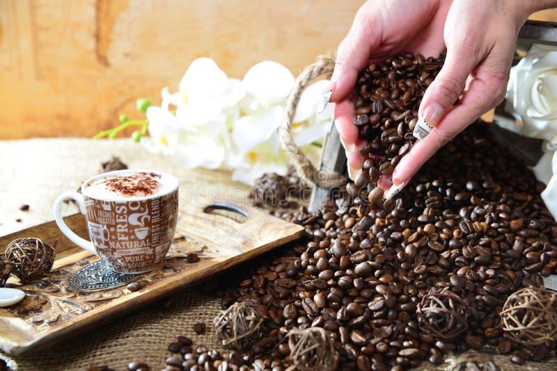 Cappuccinohand met dalende bonen royalty-vrije stock afbeeldingen
