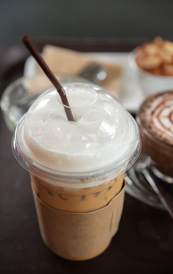 Cappuccinoiskaffe i ett exponeringsglas på den mörka trätabellen royaltyfri fotografi